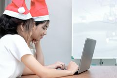 Rear view of cheerful young Asian women in Santa hats shopping online with laptop in living room at home. Merry Christmas and happ royalty free stock photography