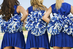 Rear View Of Cheerleaders With Pom Poms