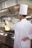 Rear view of Chef with Fingers Crossed as a Pan Catches Fire in Kitchen Royalty Free Stock Photography