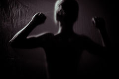 Rear view of child with raised fists in darkness Royalty Free Stock Photo