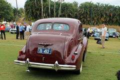 Rear view of classic american car. Rear view showing stylish trunk, bumper, tail lamps and split rear window on a burgundy 1937 buick 41 touring sedan Royalty Free Stock Photo