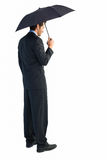 Rear view of classy businessman holding black umbrella Royalty Free Stock Photography