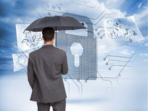 Rear view of classy businessman holding grey umbrella Stock Photo