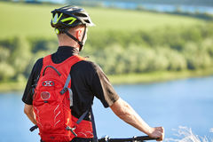 Rear view and close-up of the cyclist standing with mountain bike against river. Royalty Free Stock Images