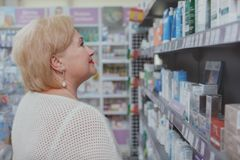 Lovely senior woman shopping at drugstore royalty free stock images