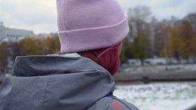 Rear view close-up of hipster woman with backpack in hat. Young beautiful woman with pink hair and pink hat on autumn stock photos