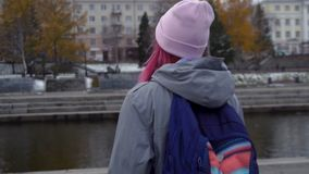 Rear view close-up of hipster woman with backpack in hat. Young beautiful woman with pink hair and pink hat on autumn royalty free stock photos