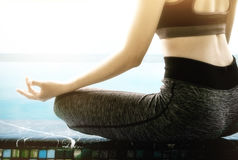 Rear view close up of woman perform meditating yoga on the swinm Stock Photography