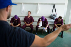 Rear view of coach discussing with baseball team Royalty Free Stock Photo
