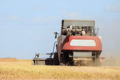 Rear view of combine harvester are working in the field Stock Photo