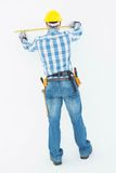Rear view of construction worker using measure tape Royalty Free Stock Images