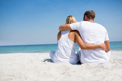Rear view of couple with arm around relaxing at beach Stock Photos