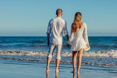 Rear View of Couple on Beach Against Clear Sky Stock Photos
