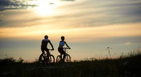 Rear view of couple cyclists riding along the road among grass with wildflowers under evening sky stock photography