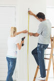 Rear view of a couple with drill and tape at new home Stock Images