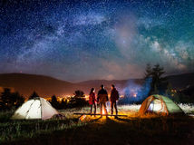 Rear view couple hikers standing near campfire in the camping Stock Image