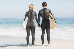 Rear view of couple holding hands on the beach Stock Photo