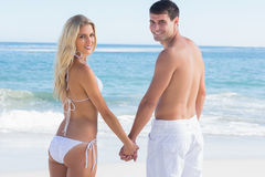 Rear view of couple holding hands looking at camera Royalty Free Stock Image