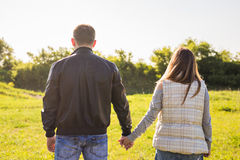 Rear view of couple holding hands walking in autumn countryside Royalty Free Stock Image