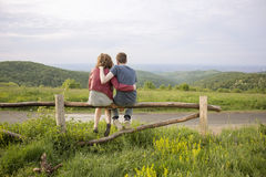Rear view couple hugging landscape. Stock Images