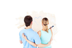 Rear view of a couple looking at a heart painting Stock Photos
