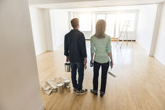 Rear View Of Couple With Paint Equipment In House Stock Photography