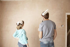 Rear View Of Couple With Paint Roller Looking At Wall Stock Image