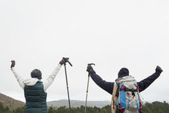Rear view of couple raising hands after a trek Stock Images