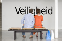 Rear view of couple reading Dutch text Veiligheid (security) and contemplating it Royalty Free Stock Photos