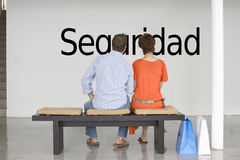 Rear view of couple reading Spanish text seguridad (security) and contemplating it Stock Images
