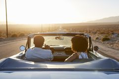 Rear View Of Couple On Road Trip Driving Classic Convertible Car Towards Sunset royalty free stock image