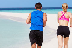Rear View Of Couple Running On Beautiful Beach Royalty Free Stock Images
