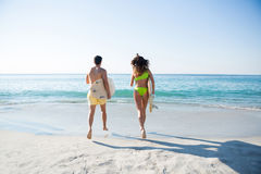 Rear view of couple running together while holding surfboards at beach Stock Photography