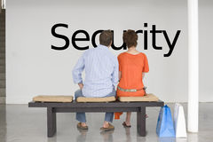 Rear view of couple seated on bench contemplating about future security Royalty Free Stock Photography