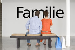 Rear view of couple seated on bench reading German text Familie (family) on wall Stock Image