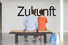 Rear view of couple seated on bench reading German text Zukunft (future) on wall Royalty Free Stock Photo