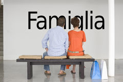 Rear view of couple seated on bench reading Italian text Famiglia (family) on wall Stock Photos