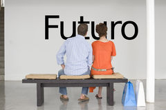 Rear view of couple seated on bench reading Spanish text Futuro (future) on wall Royalty Free Stock Image