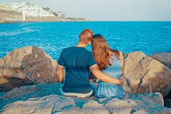 Rear View of Couple Sitting on Beach Stock Photography