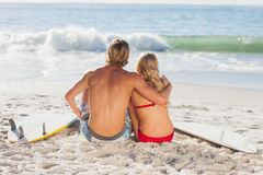 Rear view of a couple sitting on the beach and looking at the sea Stock Photography