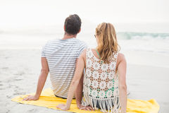 Rear view of couple sitting on the beach Stock Images