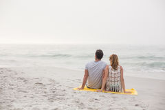 Rear view of couple sitting on the beach royalty free stock images
