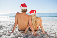 Rear view of couple sitting on beach Stock Image
