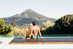 Rear view of couple sitting bu the pool Royalty Free Stock Images