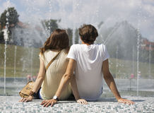 Rear view of couple sitting on fountain wall Royalty Free Stock Photography