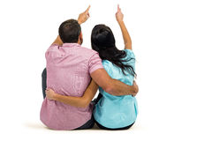 Rear view of couple sitting and pointing somewhere. On white screen Royalty Free Stock Photos
