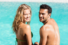 Rear view of couple sitting by the pool Royalty Free Stock Image
