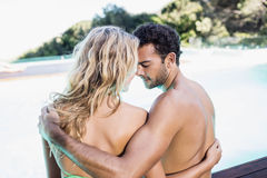 Rear view of couple sitting by the pool Royalty Free Stock Photos