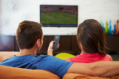 Rear View Of Couple Sitting On Sofa Watching TV Together. With Female Holding Remote Control Stock Photos