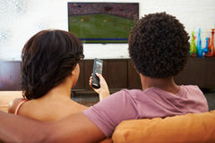 Rear View Of Couple Sitting On Sofa Watching TV Together. Rear View Of Couple At Home Sitting On Sofa Watching TV Together Holding Remote Control Stock Image